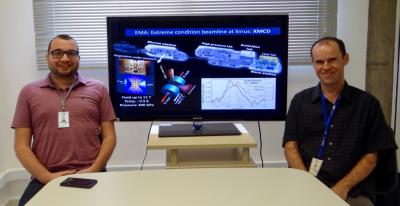 Foto dos pesquisadores Ricardo dos Reis (esquerda) e Narcizo Souza-Neto (direita), autores principais do artigo. Entre eles, na tela, o desenho da linha de luz EMA do Sirius aonde esses experimentos poderão ser realizados de forma altamente otimizada.