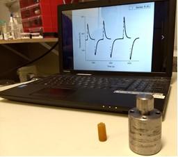 Primeiro plano: célula de pressão e amostra de borracha natural vulcanizada submetida a diversos ciclos de compressão e descompressão. Fundo: gráfico mostrando medidas de temperatura em função do tempo para diferentes variações de pressão.